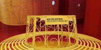 """Eine gelbe Bank steht in der Mitte des Raumes. Auf einem Schild steht: """"Nur für Rentner!"""""""