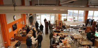 Eingangsbereich des Second Hand Kaufhauses Stilbruch in Wandsbek. Menschen stöbern zwischen Möbeln und Vasen.