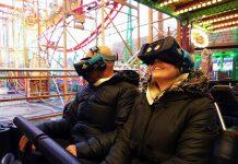 Ein Mann und eine Frau sitzen in einem Wagen der VR-Achterbahn Wilde Maus XXL.