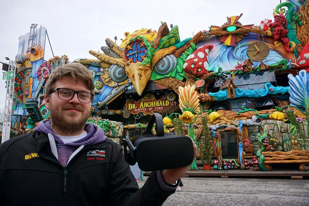 Mann steht auf dem Hamburger Frühlingsdom vor dem Fahrgeschäft Dr. Archibald und zeigt eine VR-Brille.
