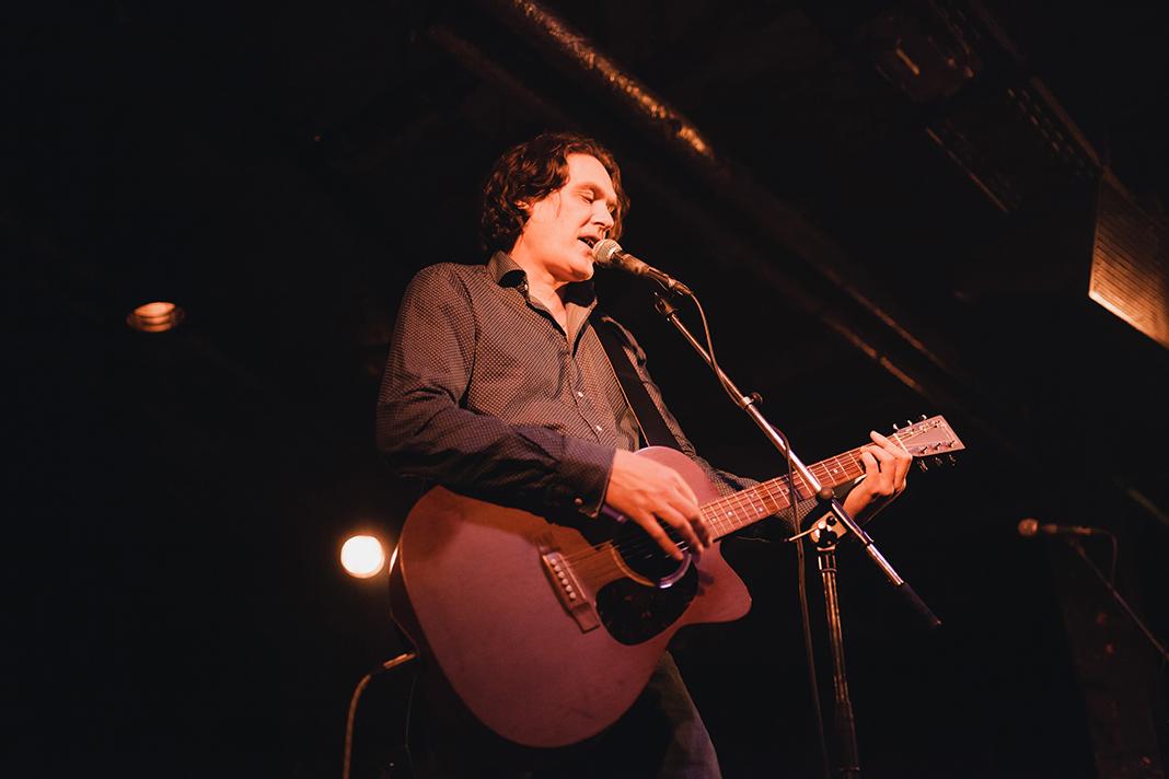 Frank Spilker von den Sternen auf der Bühne mit seiner Gitarre.