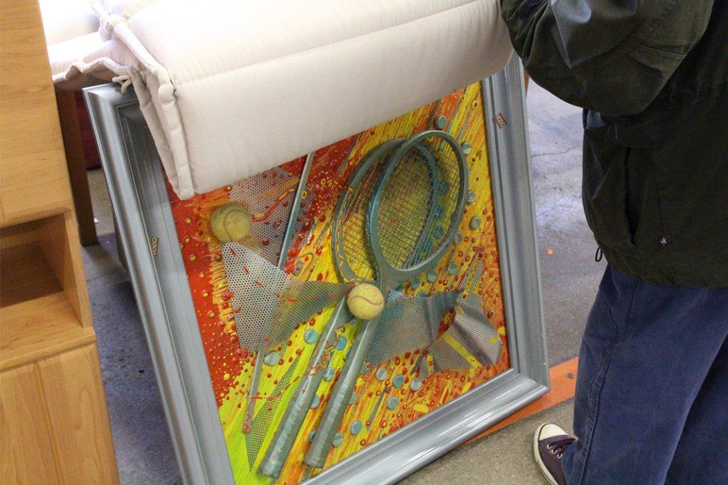 Person steht vor einem Bild, auf dem silberne Tennisschläger aufgebracht sind.