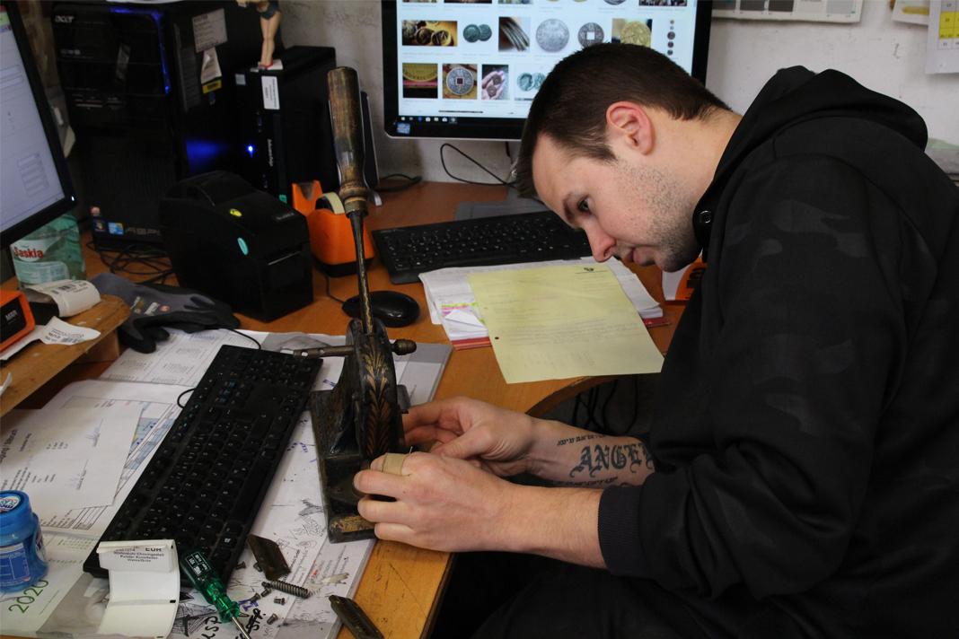 Stilbruch Lagervorarbeiter Mark Schulz sitzt an seinem Schreibtisch und untersucht eine massive Münzprägemaschine.