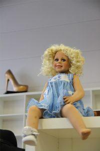 Eine Spielzeugpuppe sitzt auf einem Regal.