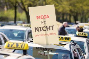 """Taxis stehen aufgereiht. Ein Taxifahrer hält aus seinem Auto ein Schild mit der Aufschrift """"Moia ist nicht genehmigungsfähig""""."""