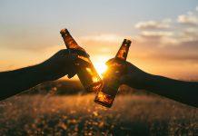 Zwei Hände mit Bierflaschen stoßen vor einem Sonnenuntergang an.