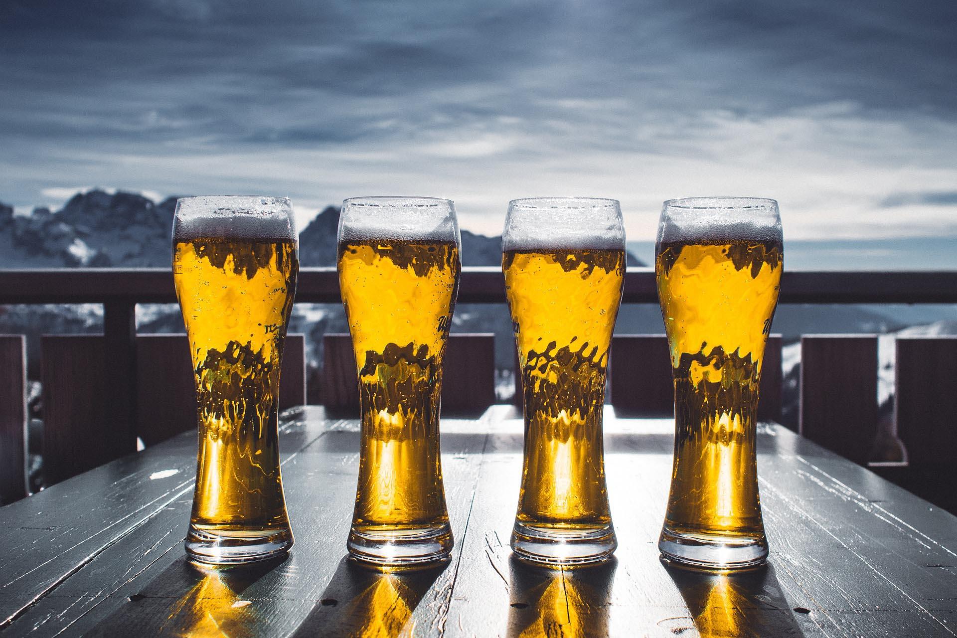 Vier gefüllte Weißbiergläser auf dem Tisch einer Biergartenterasse