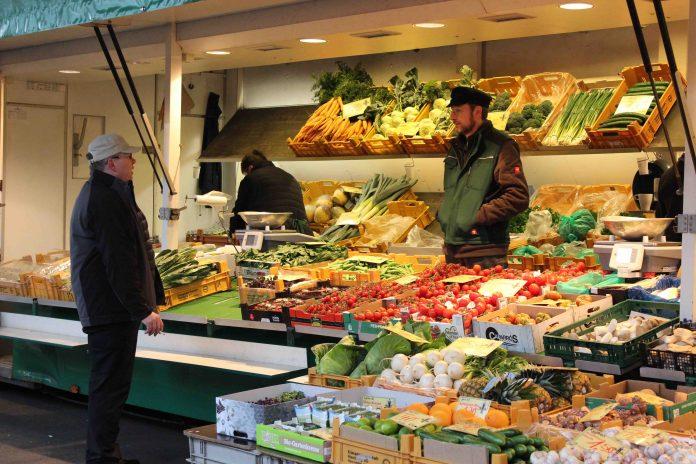 Ernst Prigge unterhält sich mit einem Kunden an seinem Obst- und Gemüsestand auf dem Isemarkt