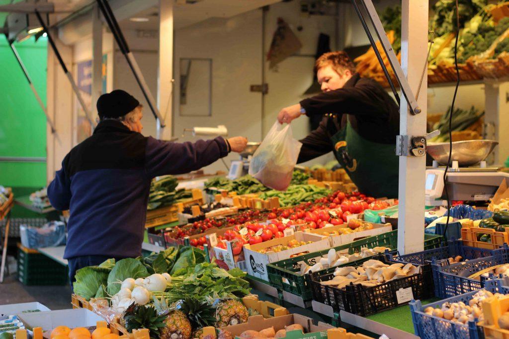 Ute Prigge überreicht Obst- und Gemüse an einen Kunden