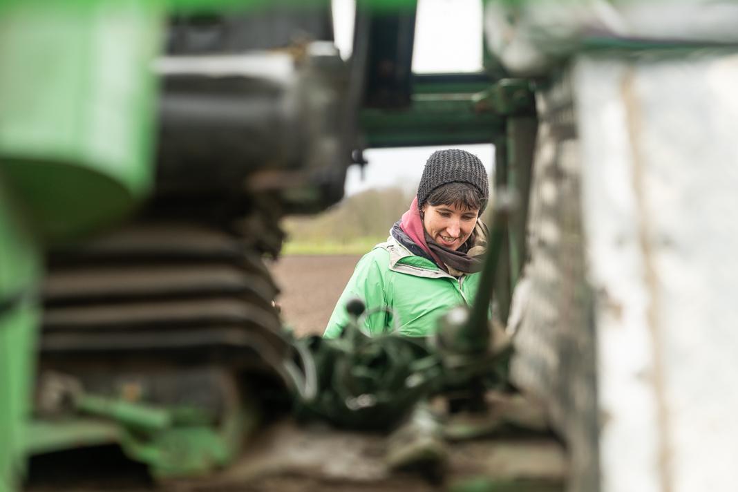 Blick durch ein Fenster des Traktors: Die Gärtnerin Bianca Rade blickt auf die Sämaschine.