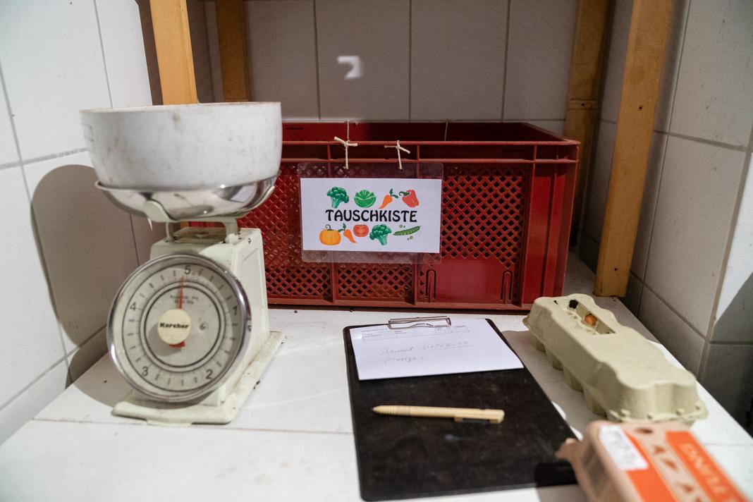 Mindestausstattung eines Solawi-Depots: Eine analoge Küchenwaage, eine rote Gemüsekiste für den Tausch von Lebensmitteln und ein Klemmbrett mit Stift und Papier für Notizen.