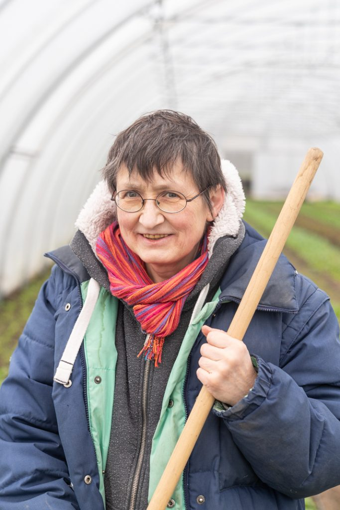 Sabine Hüholt mit einer Hacke im Gewächstunnel der Solawi Superschmelz.