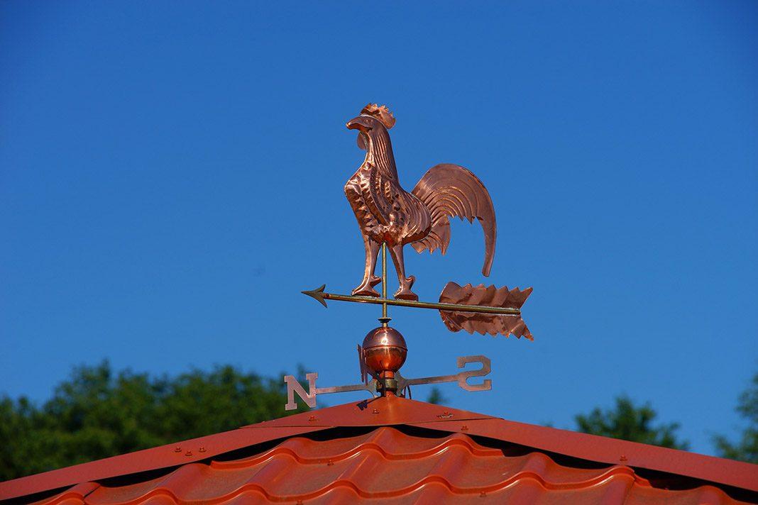 Wetterhahn aus Bronze auf dem Dach.