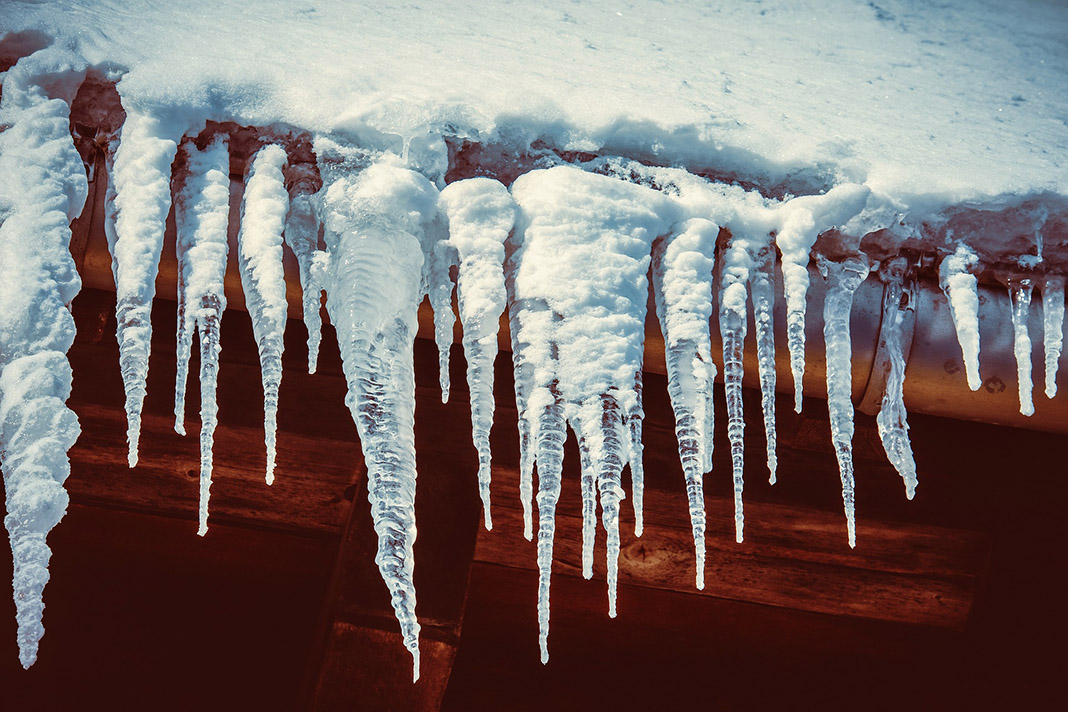 Eiszapfen haengen an einem Dach.