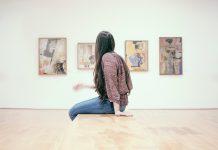 Junge Frau sitzt auf einer Bank in einer Ausstellung vor vier Bildern eines Künstlers