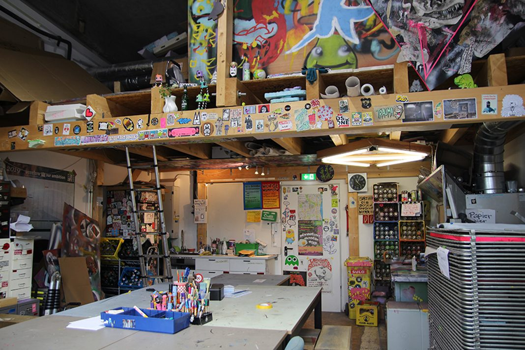 Das Atelier der Street Art School mit Tischen in der Mitte und vielen Stickern and den Wänden.