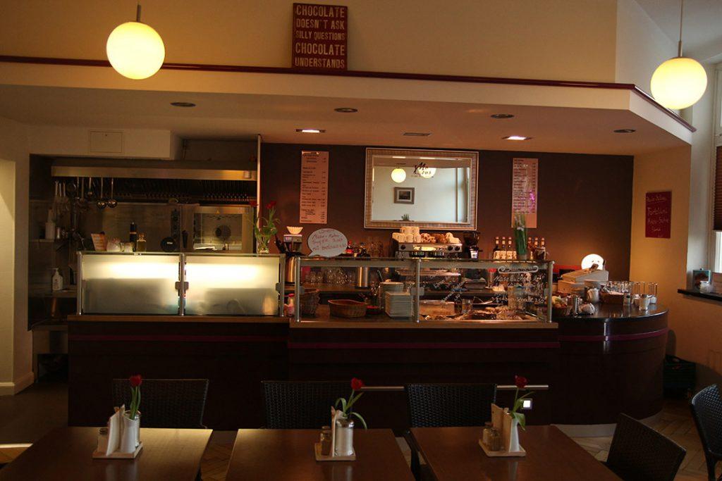 Theke des Café MaLous mit Tischen im Vordergrund