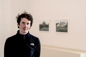Absolvent Janus Beck steht vor seinen Fotografien.