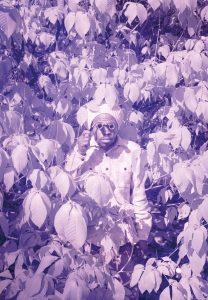 Ein Foto von Sofia Mintre zeigt einen farbigen Mann mit Fernglas im Gebüsch stehen.