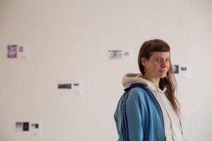 Absolventin Sofia Mintre steht vor ihrer Fotoausstellung.