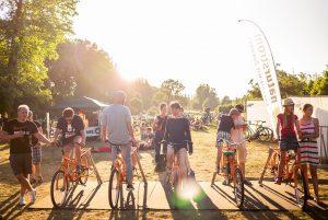 Menschen sitzen auf Fahrrädern, um mit Trittkraft die Energie für eine Bühne des Futur 2 Festivals zu produzieren.