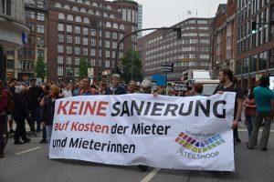 """Menschen halten auf einem Demonstrationszug ein Banner mit der Aufschrift """"Keine Sanierung auf Kosten der Mieter und Mieterinnen"""" vor sich her."""