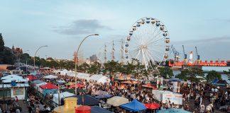 Blick auf die Hafenmeile des Hafengeburtstags 2018 mit seinen Essensständen, einem Riesenrad und einer Menschenmasse.
