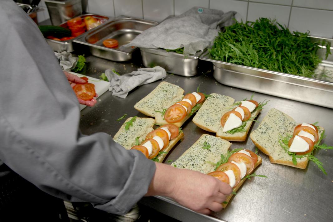 In der Küche werden Tomate-Mozzarella-Baguettes vorbereitet.