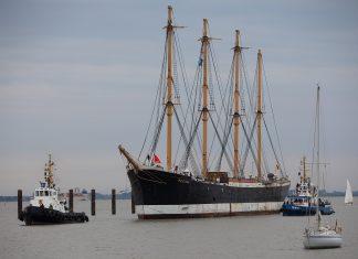 Das Museumsschiff Peking ist vor dem Stör-Sperrwerk mit Hilfe von zwei Schleppern in Richtung Peters-Werft unterwegs.
