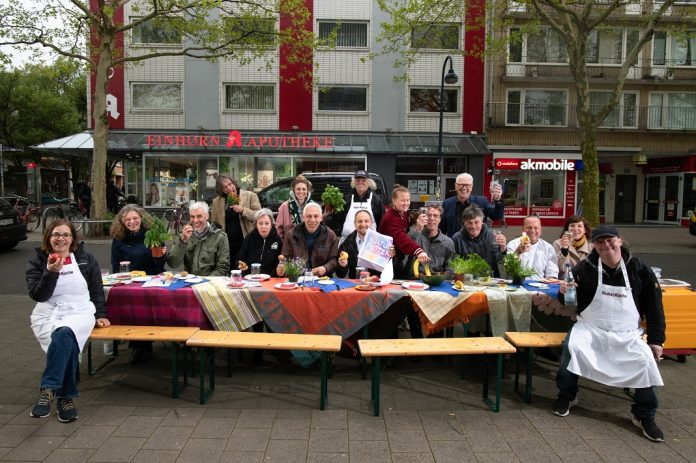 Die Kooperationspartner des Kulturfutters posieren an einer aufgebauten Essenstafel in Altona