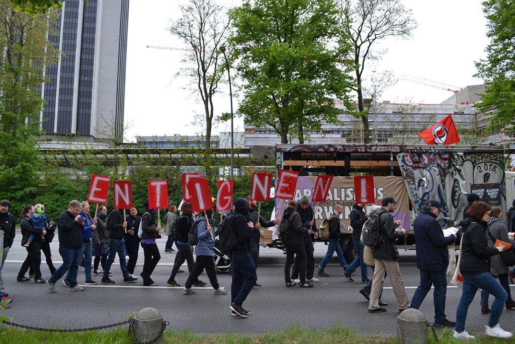 """Menschen tragen einzelne Buchstabenplakate durch Hamburgs Straßen, die das Wort """"Enteignen"""" bilden."""