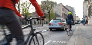 Zwei Radfahrer und ein Auto auf einer Straße. Der Radweg ist zu Ende.