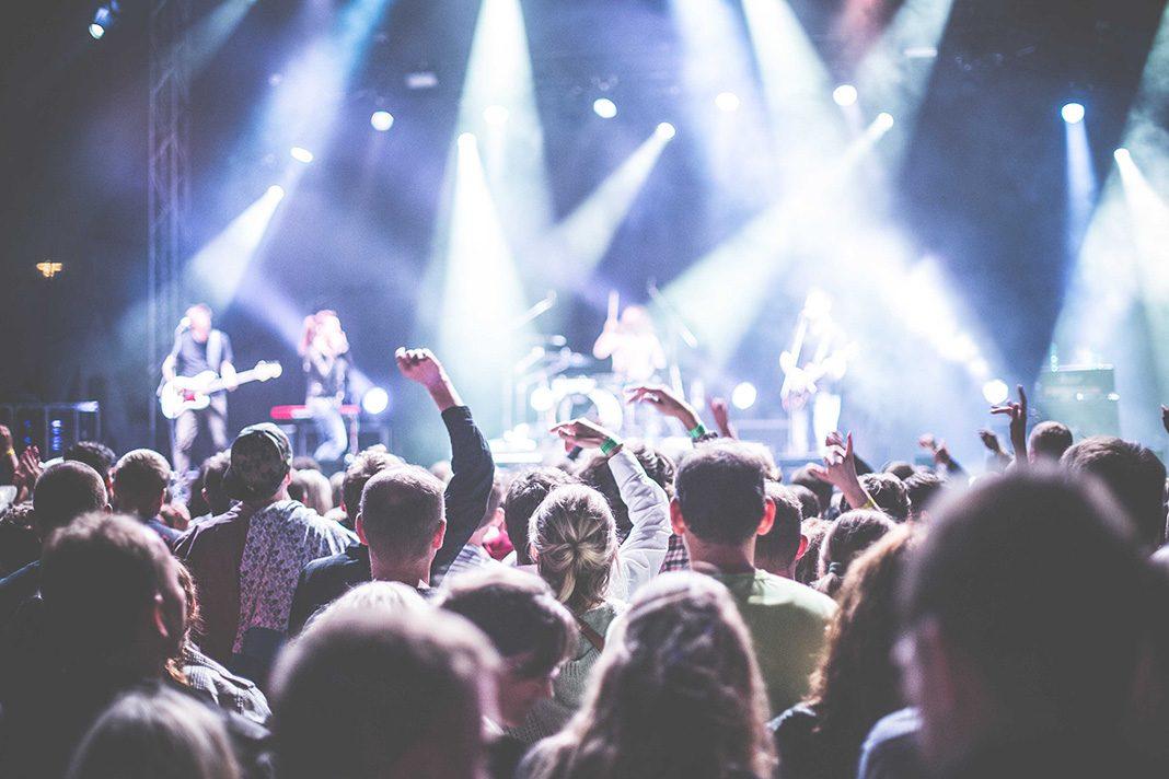 Menschen vor einer Bühne mit erhobenen Händen
