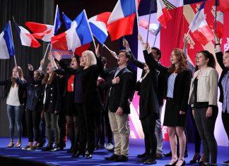 """Politiker und Wahlhelfer schwingen auf einer Bühne die französische Flagge. Eine Szene aus dem Film """"Das ist unser Land"""", präsentiert zur Europawoche."""