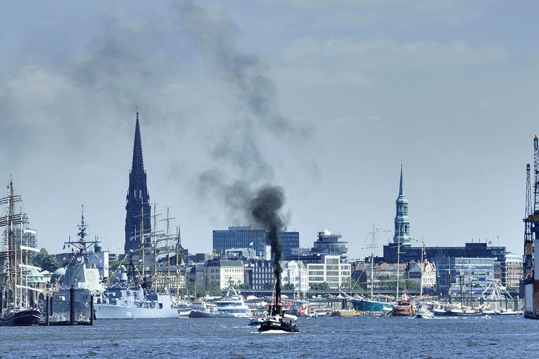 Der Schornstein eines Schiffs stößt beim Hamburger Hafengeburtstag eine dunklle Abgaswolke in den Himmel.