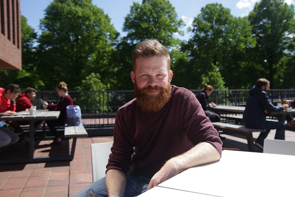 Student Laurenz Rau sitzt auf dem Sonnendeck des HAW Campus Finkenau.