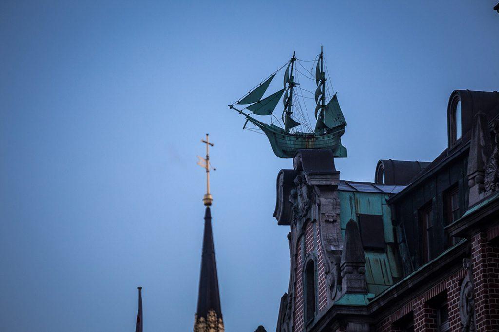 Die Skulptur eines Schiffs befindet sich auf der Dachspitze eines Hauses in der Hamburger Altstadt.