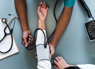 Eine Person misst den Blutdruck bei einer anderen Person.