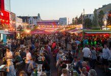 Auf dem Spielbudenplatz stehen Essens- und Getränkestände sowie Bierzeltgarnituren. Viele Menschen sind unterwegs.