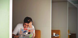 Student sitzt traurig vor seinem Laptop.