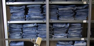 Gestapelte blaue Jeans im Regal, davor eine Nähmaschine