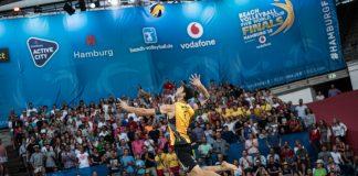 Ein Volleyballer ist im Sprung in der Luft und setzt zum Aufschlag an. Im Hintergrund sind Fans auf einer Tribüne.