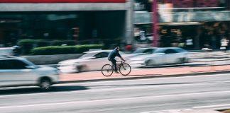 Ein Fahrradfahrer fährt auf einem Radweg zwischen zwei Straßen