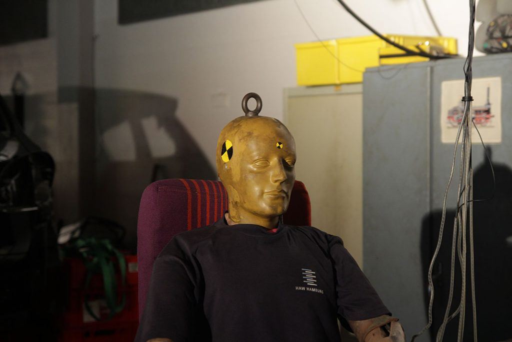 Crashtest-Dummy mit HAW-Hamburg T-Shirt in der HAWKS Werkstatt.