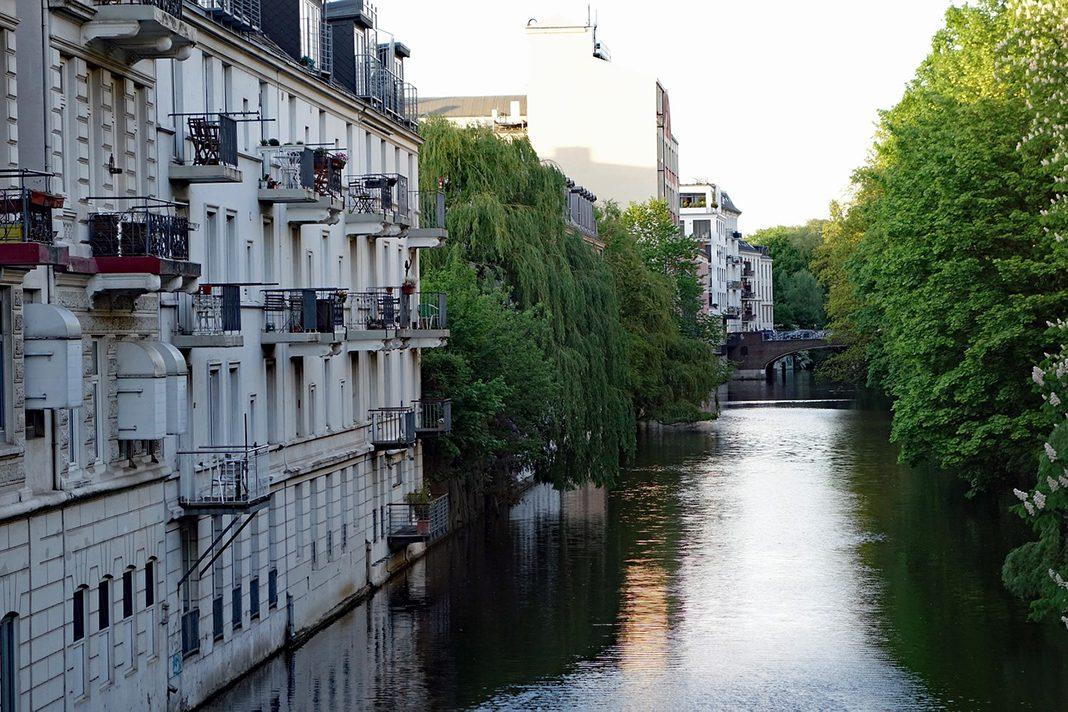 Häuserwand am Kanal in Hambrug mit grüner Bepflanzung.