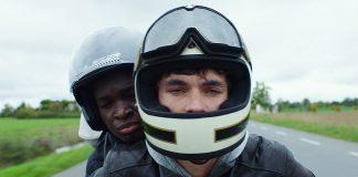 Zwei Jugendliche mit Motorradhelm auf dem Motorrad.