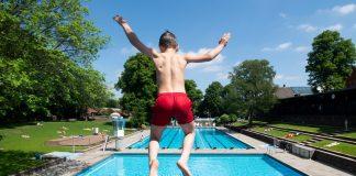 Ein Junge springt bei sonnigem Wetter im Kaifu-Bad vom Sprungturm.