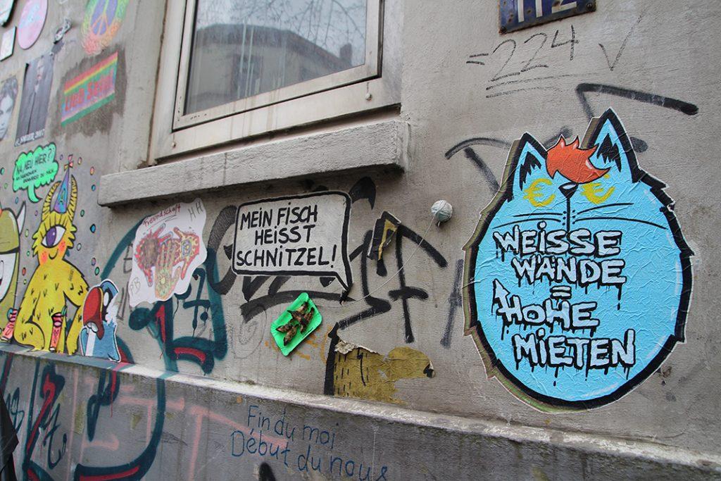 Mehrere Paste-Ups an einer grauen Wand, einige mit politischen Aussagen.