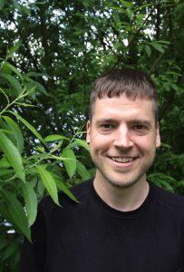 Tobias Kahrmann steht vor einem Busch und lächelt in die Kamera.