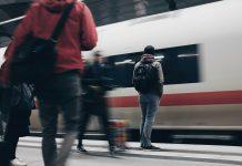 Menschen stehen am Bahnsteig vor einem einfahrenden ICE der Deutschen Bahn.